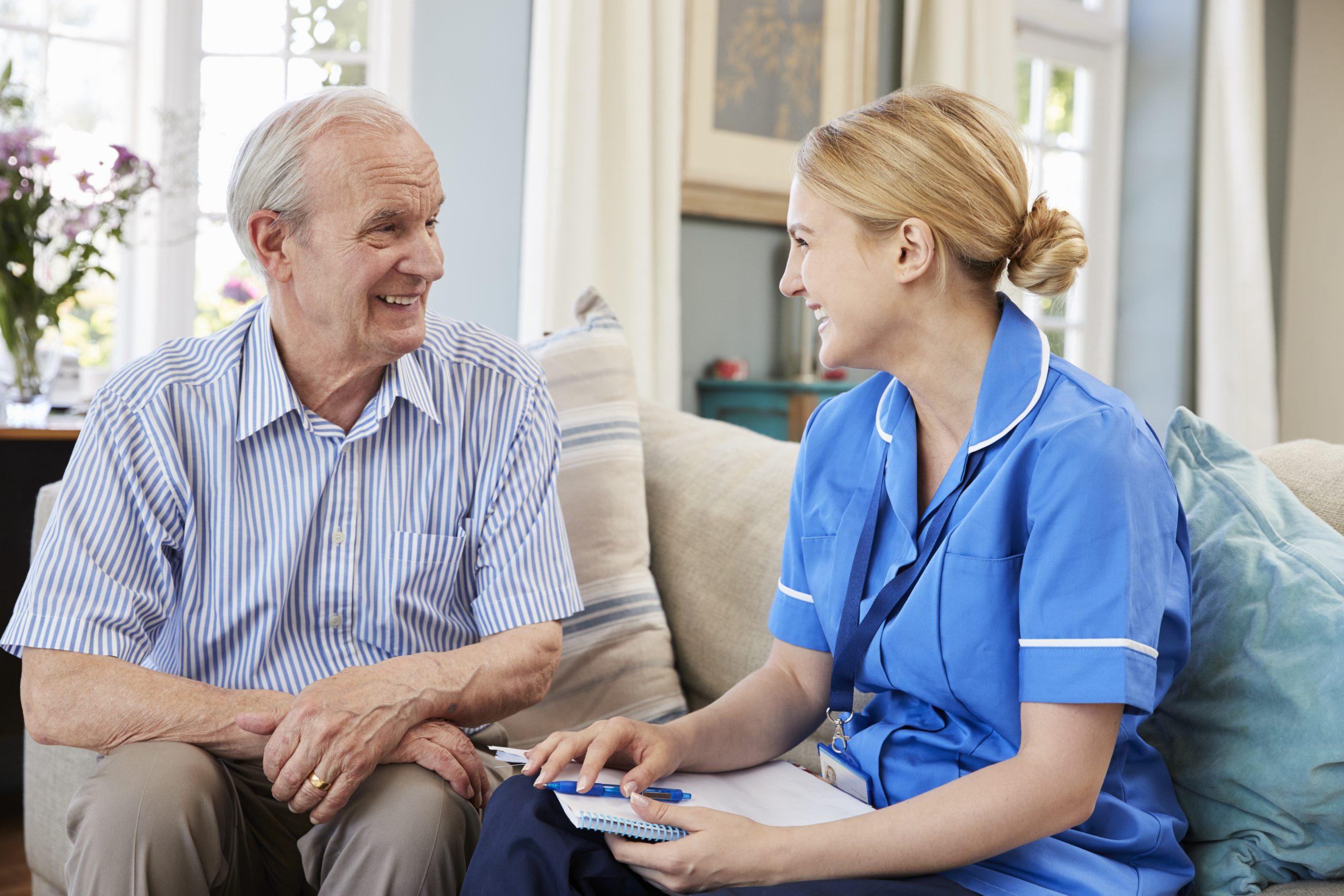 Female Community Nurse Visits Senior Man At Home;